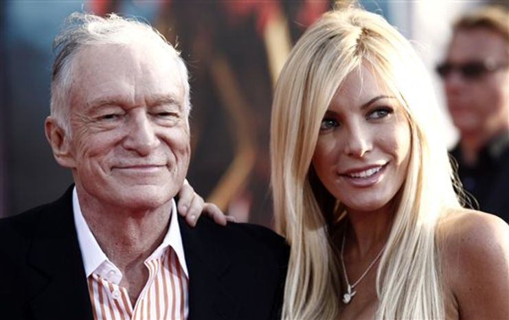 """FILE - Hugh Hefner, left, and Crystal Harris arrives at the premiere of """"Iron Man 2"""" at the El Capitan Theatre in Los Angeles in this April 26, 2010 file photo. Hefner says he's gotten engaged again. Hefner said in a Twitter message early Saturday Dec. 24, 2010 that he'd given a ring to girlfriend and Playmate Crystal Harris, saying she burst into tears. (AP Photo/Matt Sayles, File)"""