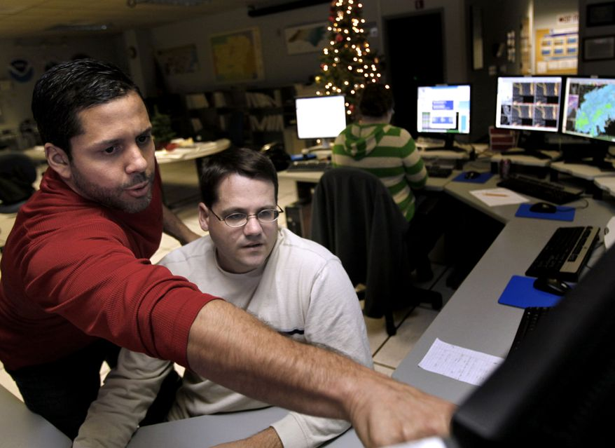 Brandon Locklear (left) and Jeff Orrock, meteorologists with the National Weather Service in Raleigh, N.C., track the snowstorm moving into the Triangle area on Saturday evening, Dec. 25, 2010. (AP Photo/The News & Observer, Takaaki Iwabu)