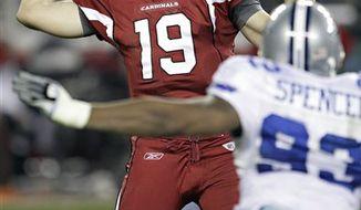 Dallas Cowboys quarterback Jon Kitna (3) scrambles as Arizona Cardinals defensive tackle Alan Branch pursues during the first quarter of an NFL football game Saturday, Dec. 25, 2010, in Glendale, Ariz. (AP Photo/Ross D. Franklin)