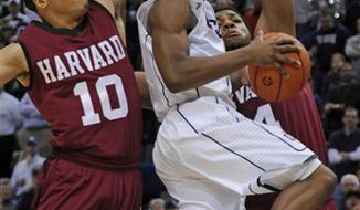 Connecticut's Kemba Walker comes in for a shot underneath Harvard's Brandyn Curry (10) and Keith Wright, right, during an NCAA college basketball game in Hartford, Conn., Wednesday, Dec. 22, 2010.  (AP Photo/Bob Child)