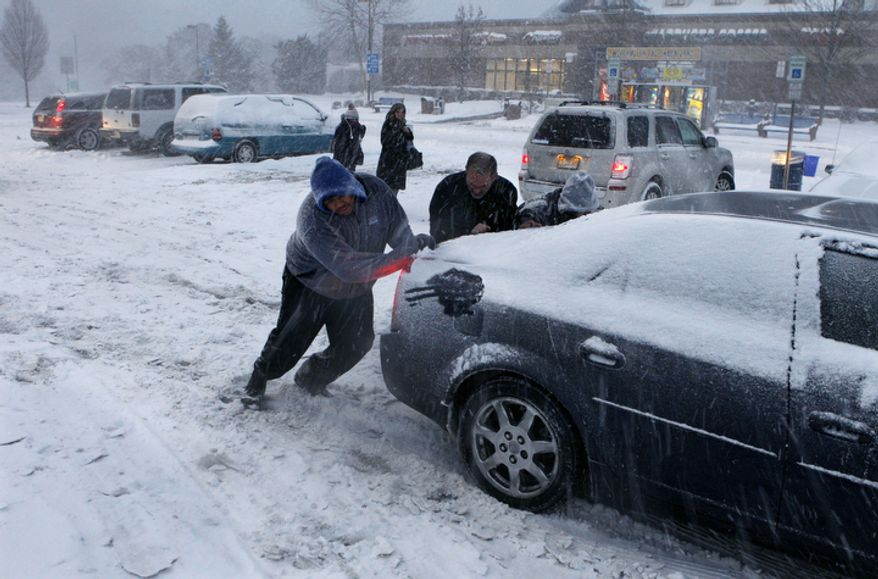 People push a car stuck in snow at the Farley rest area on the Atlantic City Expressway, near Hammonton, N.J. (AP Photo/Mel Evans)