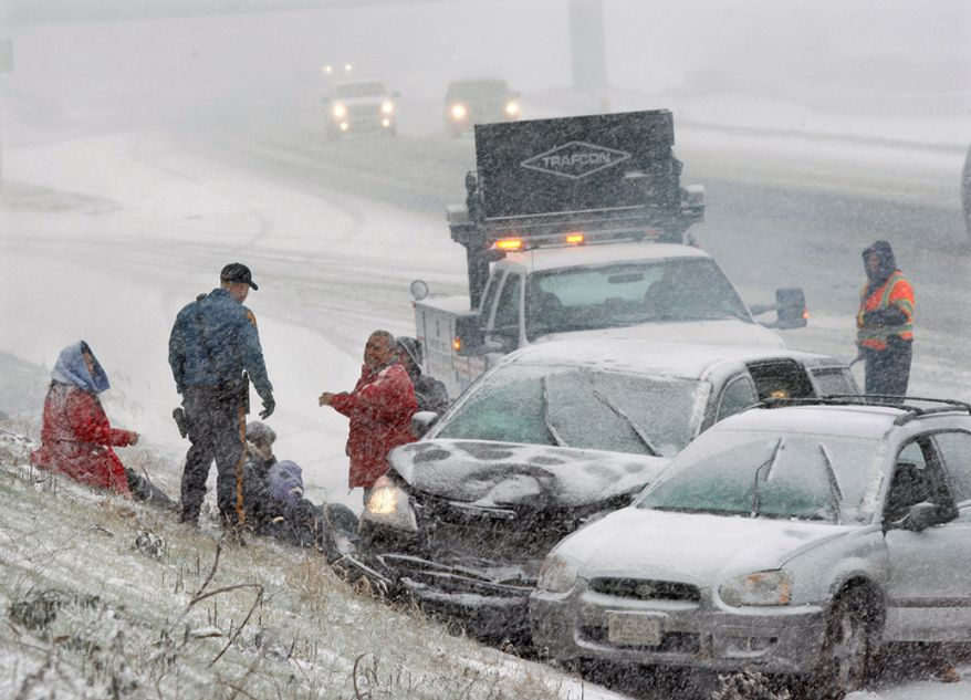 A New Jersey state trooper arrives to assist people after their cars collided in a heavy snowfall on Rt.295 near Columbus, N.J. (AP Photo/Mel Evans)