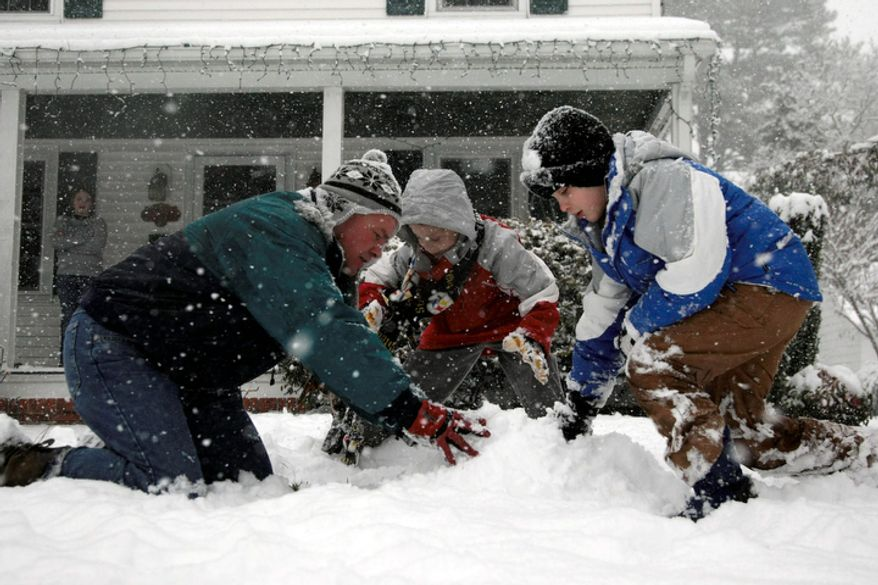 Jeff Reddish plays in the snow with his sons Elijah Reddish, 9, center and Micah Reddish, 7 outside their home off of Riverside Dr. in Salisbury, Md. (AP Photo/Salisbury Daily Times, Amanda Rippen White)