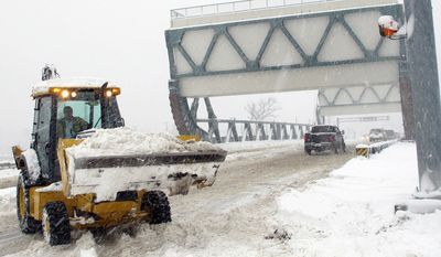 A worker uses a backhoe to clear snow from the center of the drawbridge in Great Bridge in Chesapeake, Va. (AP Photo/The Virginian-Pilot, Randall Greenwell)