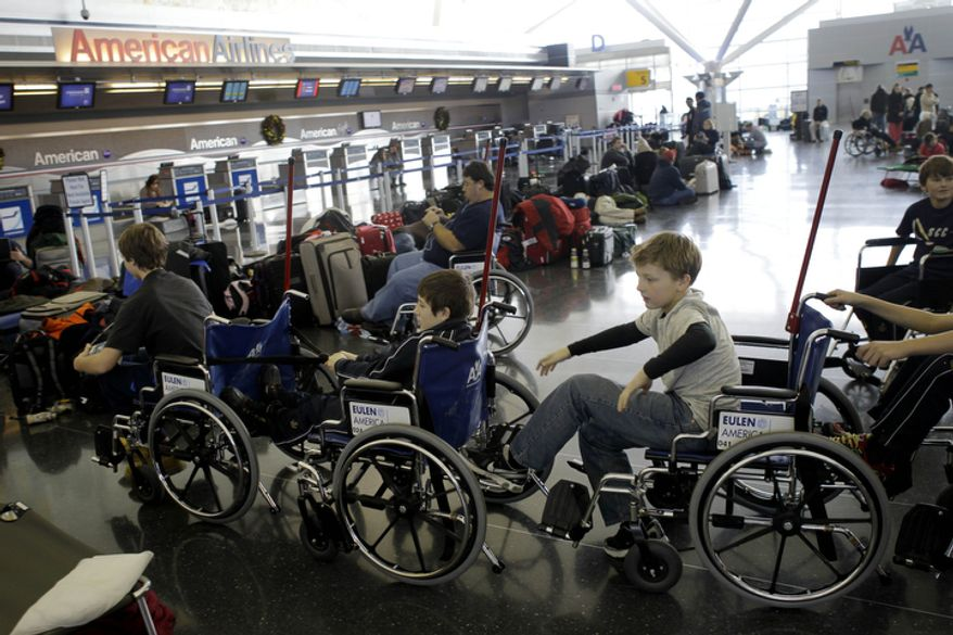 After their flight to Finland was canceled, players from the Skaneateles Bantam Finland hockey team pass the time by trying out the wheelchairs at John F. Kennedy International Airport.  (AP Photo/Seth Wenig)