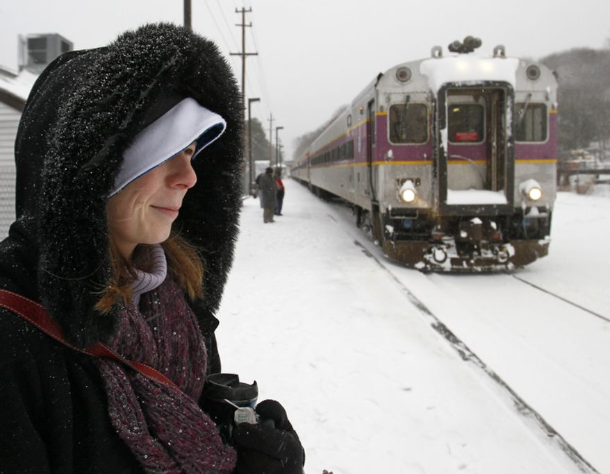 Commuter Robin Damas clutches her tea as her train arrives during a snowstorm in Andover, Mass. (AP Photo/Winslow Townson)