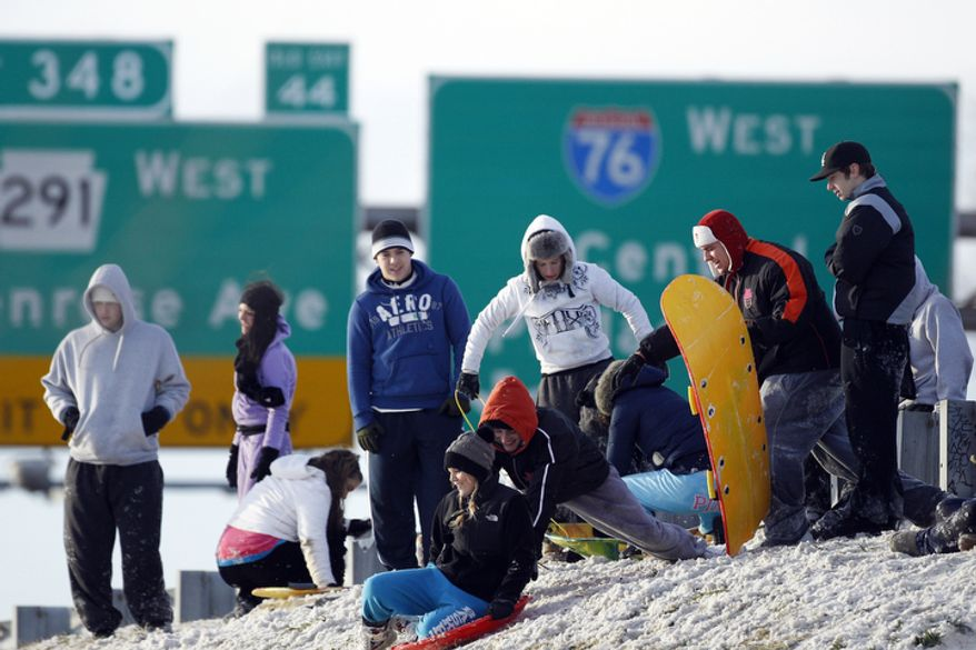 People gather to slides down a snow covered embankment next to Interstate 95 in Philadelphia. (AP Photo/Matt Rourke)
