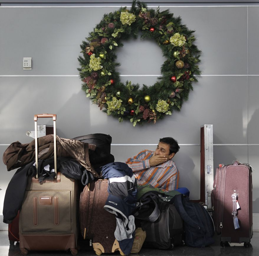 Andre Torres rests on a luggage cart while waiting to hear news about his canceled flight to Orlando, Florida at John F. Kennedy International Airport.  (AP Photo/Seth Wenig)