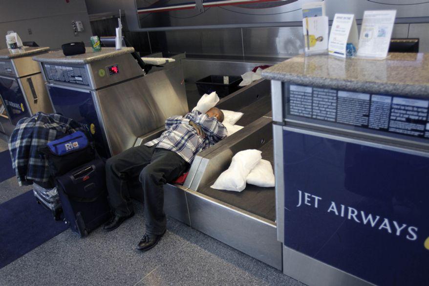 An air passenger sleeps on a luggage conveyor belt at John F. Kennedy International Airport.  (AP Photo/Seth Wenig)