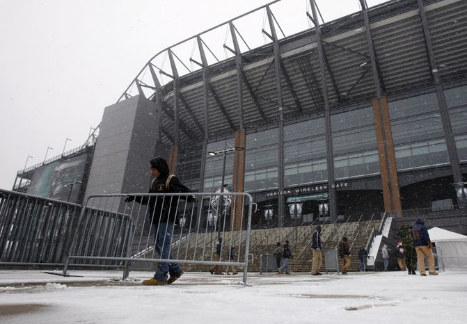 Work crews removes barriers as snow falls on Lincoln Financial Field, home of the Philadelphia Eagles football team, Sunday, Dec. 26, 2010, in Philadelphia. The Eagles game scheduled for Sunday evening against the Minnesota Vikings was postponed until Tuesday due to wintry weather. (AP Photo/Matt Slocum)