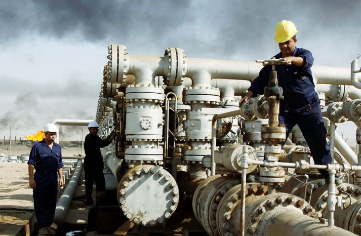 **FILE** Iraqis work at the Rumaila oil refinery near the city of Basra. The province, located on the Persian Gulf bordering Kuwait and Iran, is Iraq's only outlet to the sea and is the hub for most of Iraq's oil exports of nearly 1.9 million barrels a day to the international market. (Associated Press)