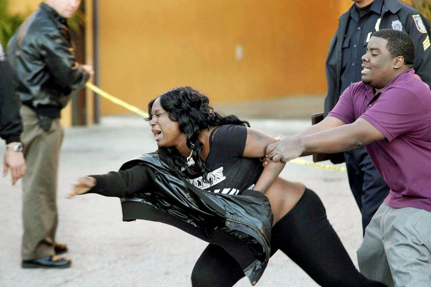 A man on Monday tries to restrain a woman reacting outside a motel room where authorities say five teenagers apparently died of carbon monoxide poisoning in Hialeah, Fla. (Associated Press)