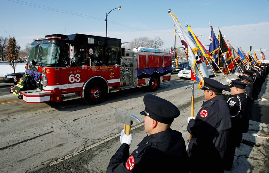 After a funeral service, the casket bearing the body of Chicago firefighter Edward J. Stringer leaves St. Rita of Cascia Chapel in Chicago on Tuesday. Fellow firefighter Corey Ankum also died last Wednesday when a roof collapsed after the fire. Ankum's funeral is scheduled Thursday. (Associated Press)