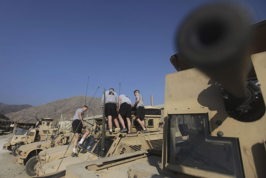 Soldiers of the U.S. 2nd Platoon, Bravo Company 2-327 check their weapons on the top of an armored vehicle at a fortress combat outpost in Kunar province in eastern Afghanistan near the Pakistani border on Monday, Dec. 27, 2010. (AP Photo/Rafiq Maqbool)