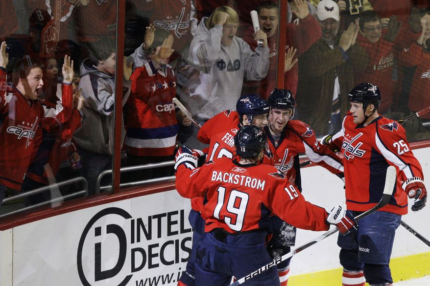 Washington Capitals fans cheer as Washington Capitals players Nicklas Backstrom (19), Eric Fehr (16), Mike Green (52), and Jason Chimera (25) celebrate Green's goal against the Montreal Canadiens during the first period of an NHL hockey game in Washington, on Tuesday, Dec. 28, 2010. (AP Photo/Jacquelyn Martin)