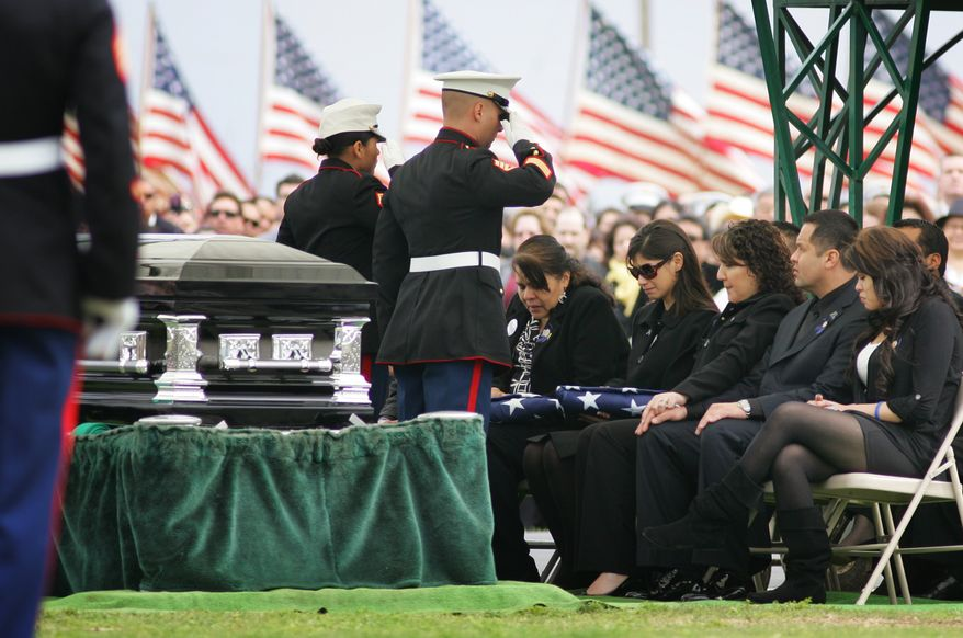 ** FILE ** Marines salute Saloma Bejar and Mariam Bejar, the mother and wife, respectively, of fallen police Officer Javier Bejar, after presenting the ceremonial flag at services in Reedley, Calif., in March 2010. (AP Photo/Gary Kazanjian, File)