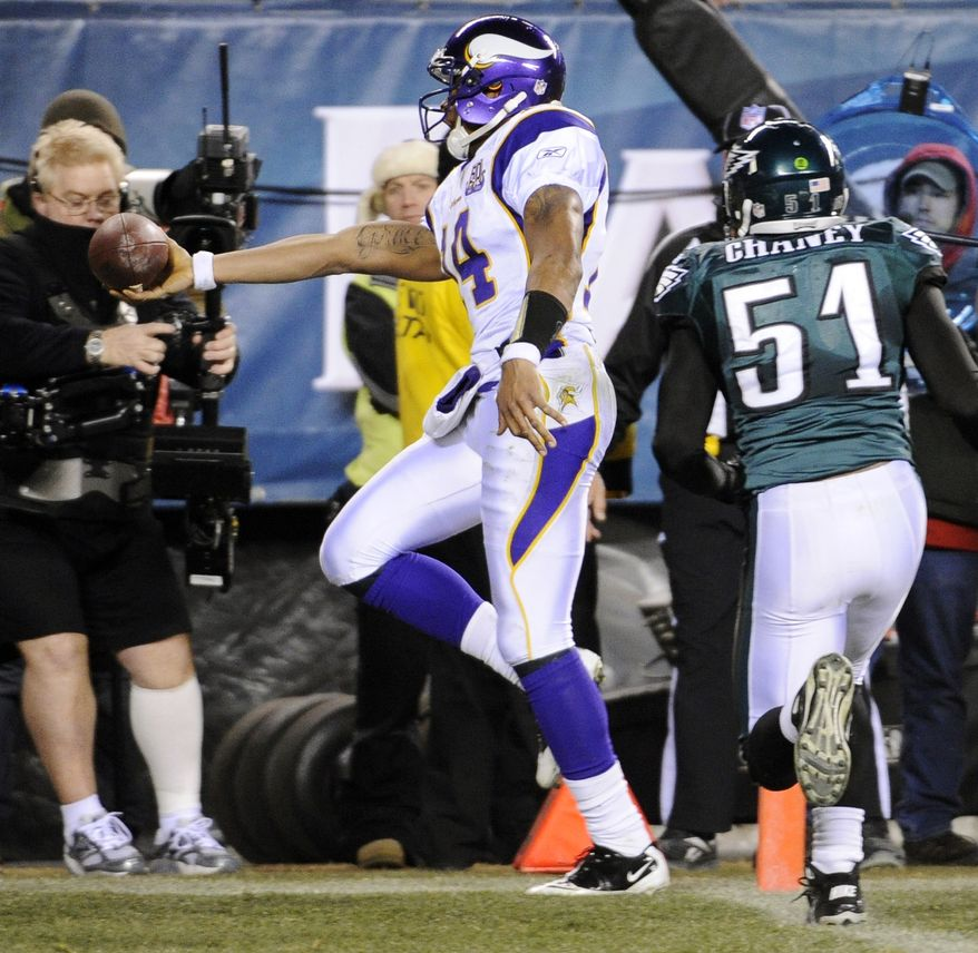 Minnesota Vikings quarterback Joe Webb (14) scores a touchdown past Philadelphia Eagles linebacker Jamar Chaney (51) in the second half of an NFL football game, Tuesday, Dec. 28, 2010, in Philadelphia. (AP Photo/Miles Kennedy)