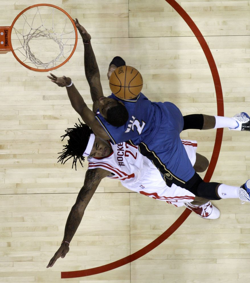Washington Wizards' John Wall (2) collides with Houston Rockets' Jordan Hill (27) as he shoots during the third quarter of an NBA basketball game Monday, Dec. 27, 2010, in Houston. The Rockets beat the Wizards 100-93. (AP Photo/David J. Phillip)