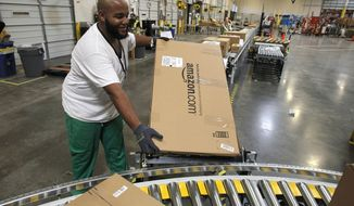 **FILE** Leacroft Green places a package to the correct shipping area at an Amazon.com fulfillment center in Goodyear, Ariz., on Nov. 11, 2010. (Associated Press)
