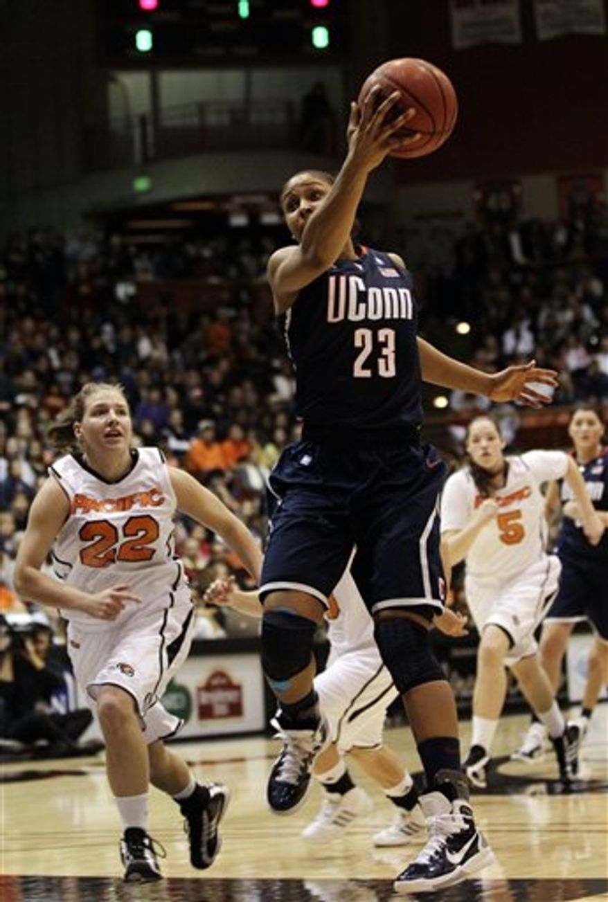 Connecticut guard Tiffany Hayes, top, shoots over Pacific guard Erica McKenzie during the first half of an NCAA college basketball game in Stockton, Calif., Tuesday, Dec. 28, 2010. (AP Photo/Marcio Jose Sanchez)