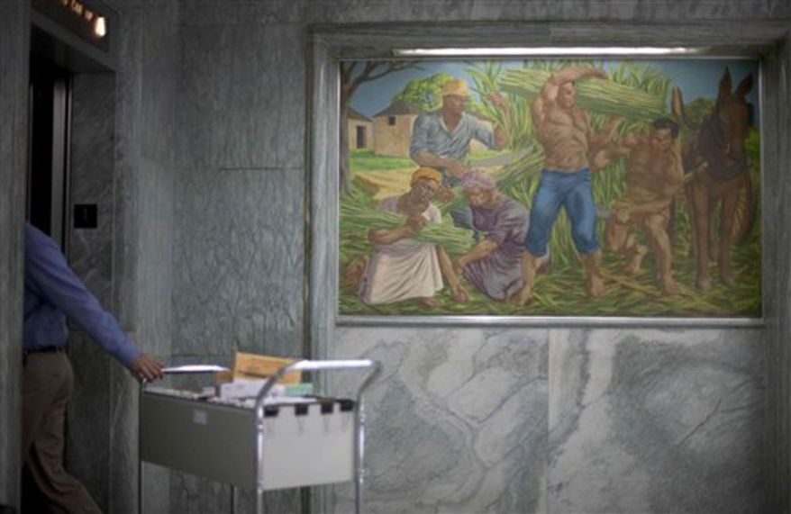 One of seven historic paintings hang in the lobby of the Georgia Department of Agriculture as a visitor checks into the security desk Tuesday, Dec. 28, 2010, in Atlanta. The incoming Georgia agriculture commissioner wants to remove the paintings including one depicting idealized versions of slavery and put them into storage when he takes office next month. Those pastel paintings have hung in the lobby of a state building for half a century without causing a stir. (AP Photo/David Goldman)