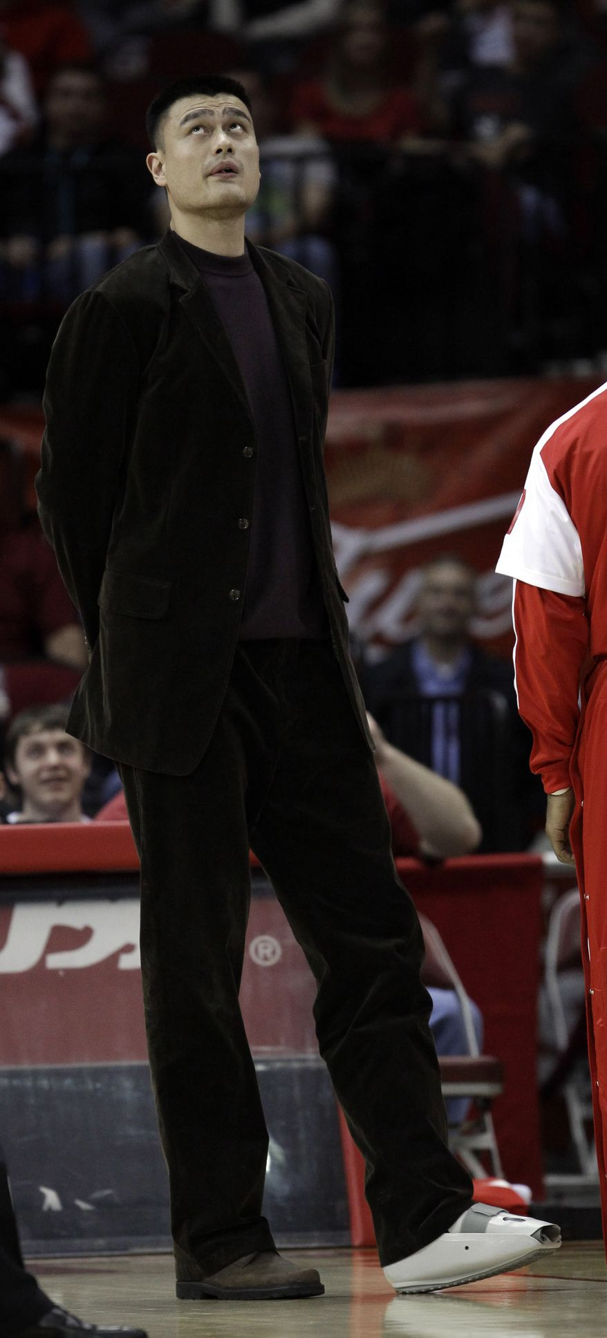 Houston Rockets center Yao Ming wears a protective boot on his left foot as he looks up at the scoreboard during the Rockets' 100-93 home win against the Washington Wizards on Dec. 27. Yao is out with a stress fracture in his left ankle. (Associated Press)