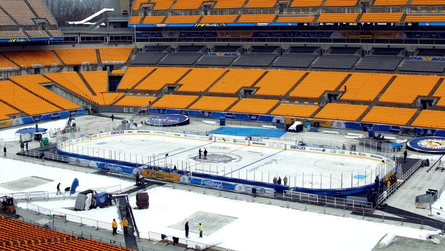"""Crews prepare Heinz Field in Pittsburgh for the """"Winter Classic"""" NHL hockey game Saturday between the Washington Capitals and the Pittsburgh Penguins. The league hopes this latest outdoor faceoff boosts TV ratings. (Associated Press)"""