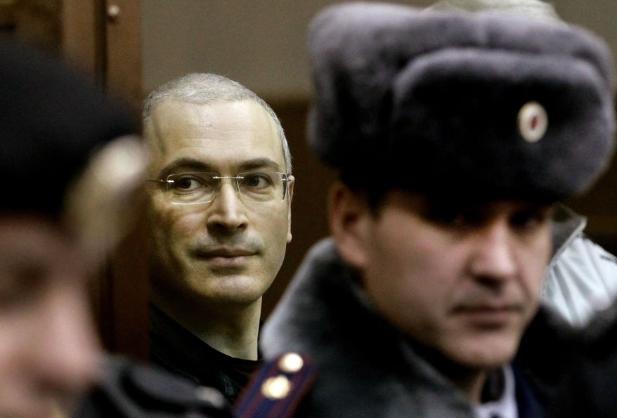 TRAPPED: Mikhail Khodorkovsky stands in a locked glass cage in the courtroom where a judge Thursday added six years to the prison term the oil tycoon is already serving. (Associated Press)
