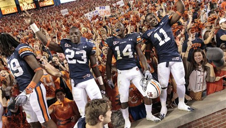 FILE - In this Saturday, Oct. 16, 2010 file photo, Auburn players Onterio McCalebb (23) Demond Washington (14) and Chris Davis (11) react after their 65-43 win over Arkansas in an NCAA college football game in Auburn, Ala. According to statistics from the Department of Education, Auburn spends $28 million on their football program. (AP Photo/Dave Martin)