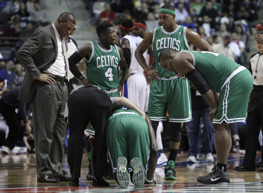 Boston Celtics forward Kevin Garnett is tended to after being injured Wednesday against the Detroit Pistons in the first quarter of the Pistons' 104-92 win in Auburn Hills, Mich. Looking on are, from left, coach Doc Rivers, Nate Robinson, Paul Pierce, and Glen Davis. (Associated Press)