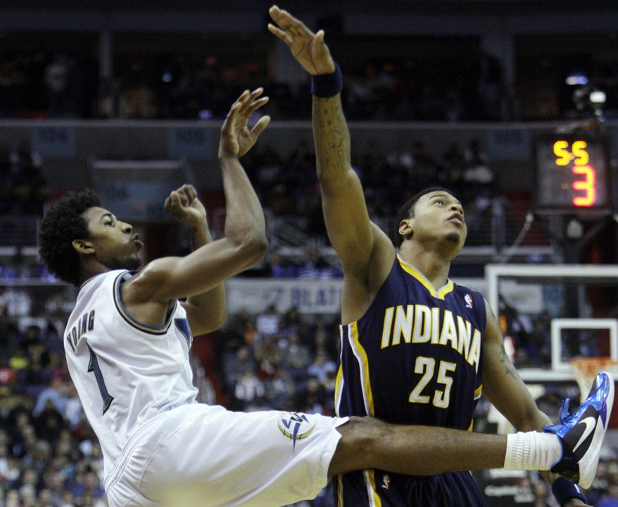 Washington Wizards guard Nick Young (1) follows through on his shot while guarded by Indiana Pacers guard Brandon Rush in the third quarter of the Wizards' 104-90 home win Wednesday. (Associated Press)