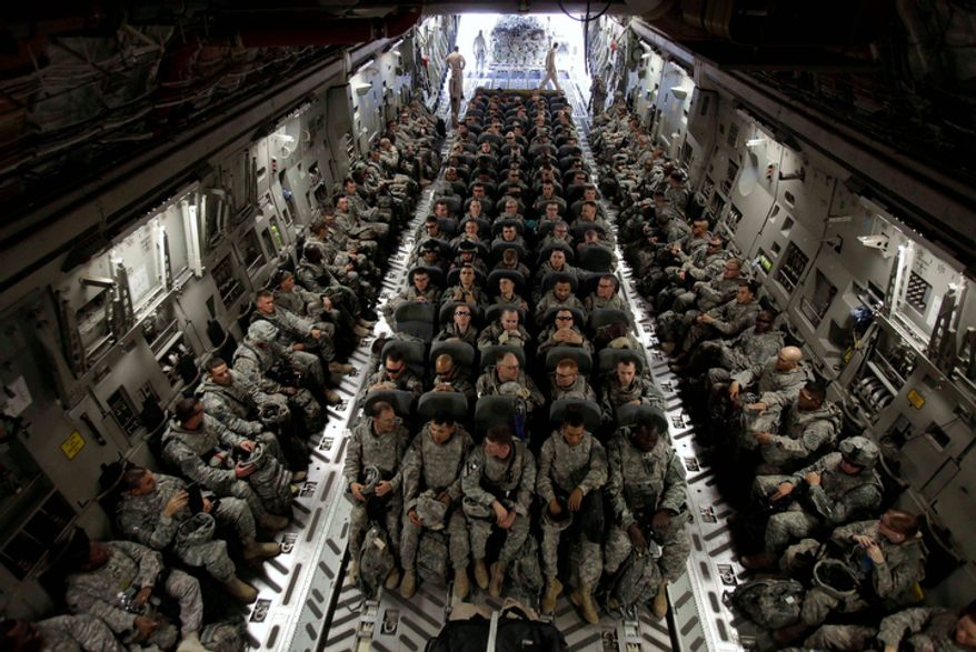 Members of 1st Brigade, 3rd Infantry Division, based at Fort Stewart, Ga., sit in the belly of a C-17 aircraft at Sather Air Base in Baghdad as they begin their journey home after a year in Iraq on Nov. 30, 2010.  (AP Photo/Maya Alleruzzo, File)