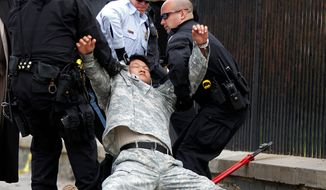 """** FILE ** Dan Choi (center) falls as he is arrested for handcuffing himself to the fence outside the White House in Washington during a protest against the military's """"don't ask, don't tell"""" policy on Nov. 15, 2010. (AP Photo/Pablo Martinez Monsivais, File)"""