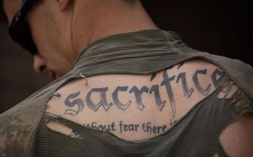 "A tattoo on the back of U.S. Army Sgt. James Wilkes of Rochester, N.Y., is seen through his torn shirt after a foot patrol with the 1st Platoon, Charlie Company, 2nd Battalion, 1st Infantry Regiment of the 5th Styker Brigade in Afghanistan's Kandahar province on May 8, 2010. The full tattoo reads: ""Sacrifice. Without fear there is no courage."" (AP Photo/Julie Jacobson)"