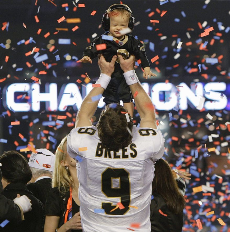 New Orleans Saints quarterback Drew Brees (9) holds his son Baylen after the NFL Super Bowl XLIV football game against the Indianapolis Colts on Feb. 7, 2010 in Miami. The Saints won 31-17. (AP Photo/Eric Gay, File)