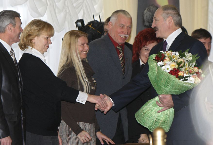 Belarusian President Alexander Lukashenko greets officials of the election commission as he prepares to vote in presidential elections, at a polling station in the Belarusian capital, Minsk, Sunday, Dec. 19, 2010. (AP Photo/Sergei Grits)