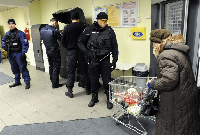 Bank staff, guarded by members of a Special Police Unit, fill cash machines with euro currency in Tallinn, Estonia, on Thursday, Dec. 30, 2010. Estonia was gearing up Friday for historic New Year's festivities as the tiny country becomes the first former Soviet republic to adopt the euro, a symbolic boost for the currency tarnished by the worst crisis in its 12-year history. (AP Photo/Timur Nisametdinov, NIPA)