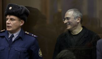 Mikhail Khodorkovsky (right) reacts after being sentenced to six more years in prison in a courtroom in Moscow on Thursday, Dec. 30, 2010. (AP Photo/Alexander Zemlianichenko)