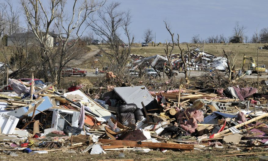 The remains of a home, foreground, and a fire station, background, are shown after a tornado tore through the small town of Cincinnati, Ark., early in the morning on Friday, Dec. 31, 2010. (AP Photo/April L. Brown)