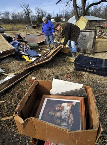 Margie Sisemore, left, and Tammy Borden, right, clean up in the aftermath of a tornado that tore through the small town of Cincinnati, Ark., in western Washington County early in the morning on Friday, Dec. 31, 2010. A tornado fueled by an unusually warm winter air sliced through parts of northwestern Arkansas early on New Year's Eve, killing three people, injuring several others and knocking out power to thousands of homes and businesses. (AP Photo/April L. Brown)