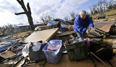 Margie Sisemore cleans up after a tornado destroyed several homes in the small town of Cincinnati, Ark., in western Washington County early in the morning on Friday, Dec. 31, 2010. A tornado fueled by an unusually warm winter air sliced through parts of northwestern Arkansas early on Friday. (AP Photo/April L. Brown)