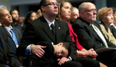Vincent C. Gray's grandson Austin Gray, 5, rests on the lap of his father, and Vincent Gray's son-in-law Stacy Tucker, as Washington D.C. Mayor Vincent C. Gray delivers his inauguration speech at the Walter E. Washington Convention Center in Washington D.C., Sunday January 2, 2011.  (Rod Lamkey Jr / for The Washington Times)