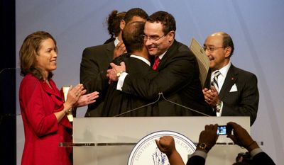 With his daughter Jonice Gray Tucker, left, looking on, Vincent C. Gray, center, gets a hug from  Eric Washington, Chief Judge, District of Columbia Court of Appeals, after taking the oath of office of mayor. Mayor Gray, a native of D.C., is the sixth elected mayor of the District of Columbia, and succeeds Mayor Adrian Fenty. (Rod Lamkey Jr / for The Washington Times)