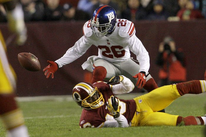 New York Giants safety Antrel Rolle (26) scrambles for the ball after knocking it from Washington Redskins wide receiver Anthony Armstrong (13) during the first half of an NFL football game in Landover, Md. on Sunday, Jan. 2, 2011. (AP Photo/Jacquelyn Martin)