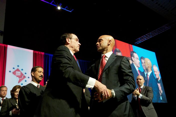 PASSING THE TORCH: D.C. Mayor Vincent C. Gray receives a hug from former Mayor Adrian M. Fenty after his inaugural address at the Washington Convention Center on Sunday. (Rod Lamkey Jr./Special to The Washington Times)