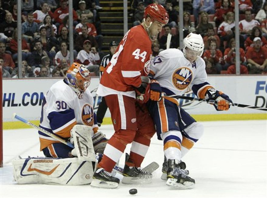 New York Islanders goalie Dwayne Roloson (30) stops a shot as Andrew MacDonald (47) defends Detroit Red Wings right wing Todd Bertuzzi (44) in the second period of an NHL hockey game in Detroit on Friday, Dec. 31, 2010. (AP Photo/Paul Sancya)