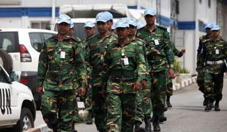U.N. troops walk inside their compound in Abidjan, Ivory Cost, on Friday, Dec. 31, 2010. The United Nations has warned supporters of incumbent leader Laurent Gbagbo that an attack on the hotel where the internationally recognized winner of last month's election is based could reignite civil war. (AP Photo/Sunday Alamba)