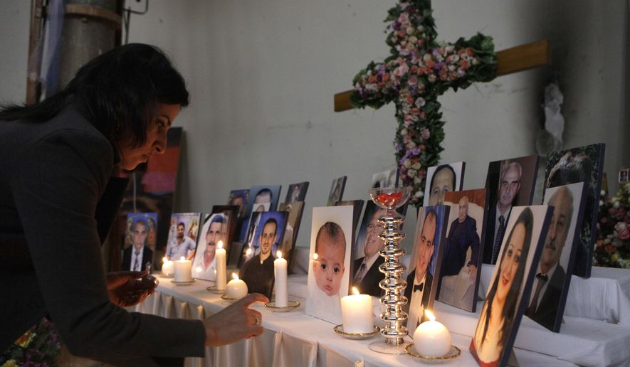 A woman lights a candle among pictures of slain Iraqi Christians at Our Lady of Salvation church in Baghdad on Friday, Dec. 31, 2010. Muslim militants took 120 hostages at the church on Oct. 31 in a siege that left 68 dead. (AP Photo/Khalid Mohammed)