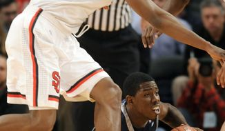 Georgetown's Henry Sims, bottom, tries to pass the ball under defensive pressure from St. John's Justin Brownlee in the first half of an NCAA college basketball game at Madison Square Garden in New York, Monday, Jan. 3, 2011. (AP Photo/Henny Ray Abrams)