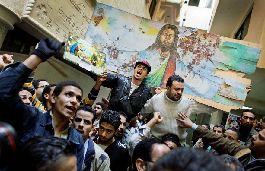 """""""With our blood and soul, we redeem the cross,"""" Coptic Christians chant after Mass on Sunday, Jan. 2, 2011, at Saints Church in Alexandria, Egypt, where 21 were killed by a suicide bomber. They carried a blood-spattered poster depicting Jesus. (AP Photo)"""